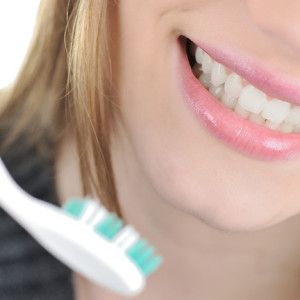 Woman with toothbrush representing dentistry.